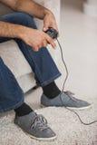 Sezione bassa di un uomo che gioca i video giochi in salone Immagine Stock Libera da Diritti