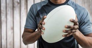 Sezione del giocatore di rugby metà di contro il pannello di legno confuso Fotografia Stock