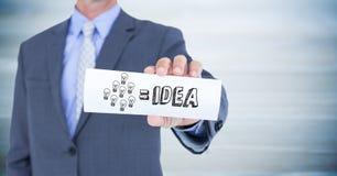 Sezione dell'uomo di affari metà di con la carta che mostra scarabocchio grigio di idea contro il pannello di legno blu confuso Fotografia Stock