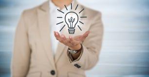 Sezione della donna di affari la metà di con distribuiscono ed il grafico della lampadina con il chiarore contro legno blu confus Immagini Stock Libere da Diritti
