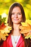 Sezon jesienny. Portret dziewczyny kobieta trzyma jesiennych liście w parku Zdjęcie Stock