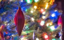 Sezon wakacyjny, choinek dekoracje jarzy się pod świecącymi, żywymi i kolorowymi światłami na małego faux salowym drzewie, Obraz Stock