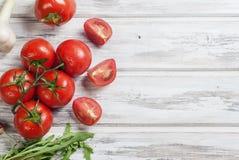 Sezonowi warzywa, czereśniowi pomidory na gałąź, liście aru Zdjęcia Royalty Free