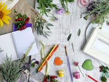 Sezonowy dekoracyjny skład kwiaty, jagody, sztuka i klerykalni materiały, serca robić odczuwany na tle lekki drewno obraz stock