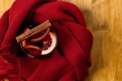 Sezonowy i wakacje pojęcia boże narodzenie rozmyślający wino z pięknymi pomarańcze plasterkami wśrodku szkła, zakrywającego z cie obrazy stock