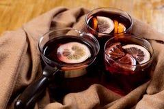 Sezonowy i wakacje pojęcia boże narodzenie rozmyślający wino z pięknymi pomarańcze plasterkami wśrodku szkła, zakrywającego z cie obrazy royalty free