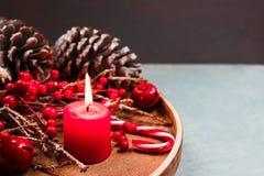 Sezonowy i wakacje pojęcie Dekoracyjny skład z świeczką, jedlinowi rożki, zimy tło Selekcyjna ostrość obraz royalty free
