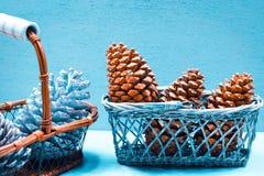 Sezonowy i wakacje pojęcie Jedlinowi rożki w rocznika koszu na błękitnym lodowym zimy tle Selekcyjna ostrość obraz royalty free
