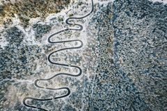Sezonowy krajobraz wijąca droga otaczająca śniegiem w lesie zdjęcia royalty free