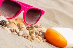 Sezonowy pojęcie, rozsypisko skorupy, okulary przeciwsłoneczni i słońce płukanka, Fotografia Royalty Free