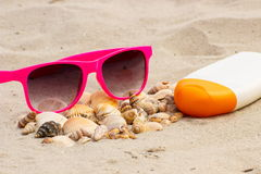 Sezonowy pojęcie, rozsypisko skorupy, okulary przeciwsłoneczni i słońce płukanka na piasku przy plażą, Obraz Stock