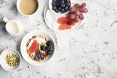 Sezonowy zdrowy śniadanie: jogurt, czekoladowy granola, różowy grapefruitowy, winogrona, pistacja Odgórnego widoku kopia obraz stock