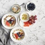 Sezonowy zdrowy śniadanie: jogurt, czekoladowy granola, różowy grapefruitowy, winogrona, pistacje Odgórny widok kosmos kopii mies Obrazy Royalty Free