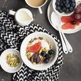 Sezonowy zdrowy śniadanie: jogurt, czekoladowy granola, różowy grapefruitowy, winogrona, pistacje Odgórny widok kosmos kopii mies Zdjęcie Stock