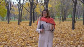 Señora Walks On The Autumn Park Holding una carpeta o un ordenador portátil y una taza de café almacen de video