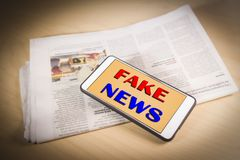 Sfałszowani wiadomości słowa na ekranie nad gazetą Sfałszowana wiadomość, bajerowania pojęcie zdjęcie stock