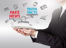 Sfałszowany wiadomości informaci pojęcie Młody człowiek trzyma pastylkę komputerowa obraz stock