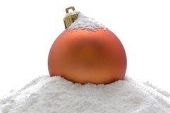 Sfera arancione di natale in neve Fotografie Stock