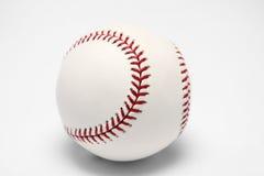 Sfera bianca di baseball su una priorità bassa bianca Fotografia Stock