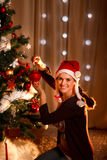 Sfera d'attaccatura di natale della donna sull'albero di Natale Fotografia Stock