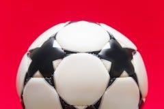 Sfera di calcio bianca su una priorità bassa rossa Fotografia Stock Libera da Diritti