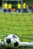 Sfera di calcio nella rete al campo immagini stock