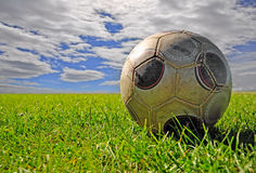 Sfera di calcio sul campo contro cloudscape Fotografie Stock Libere da Diritti