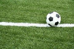 Sfera di calcio sul campo di calcio con la riga della curva Fotografia Stock