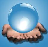 Sfera di cristallo blu lucida in mani Fotografia Stock