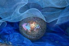Sfera di cristallo con la carta di Creta del blu e del reticolato fotografia stock