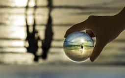 Sfera di cristallo nella riflessione del mare sul baciare delle coppie Fotografia Stock Libera da Diritti