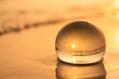 Sfera di cristallo sulla spiaggia con le onde del mare ad alba di mattina thailand immagini stock libere da diritti