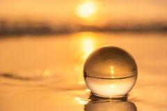 Sfera di cristallo sulla spiaggia con le onde del mare ad alba di mattina thailand fotografia stock