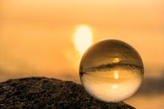 Sfera di cristallo sulla spiaggia con le onde del mare ad alba di mattina thailand immagine stock