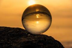 Sfera di cristallo sulla spiaggia con le onde del mare ad alba di mattina thailand fotografia stock libera da diritti