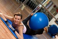 Sfera di esercitazione di Pilates fra i suoi piedini Immagini Stock Libere da Diritti