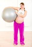 Sfera di forma fisica della holding della donna incinta in mani Immagini Stock Libere da Diritti