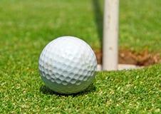 Sfera di golf al foro Fotografie Stock