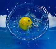 Sfera di golf che spruzza in acqua Fotografie Stock