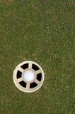 Sfera di golf nel foro Immagine Stock