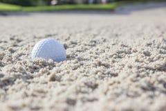 Sfera di golf nel separatore di sabbia Fotografie Stock