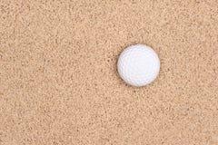 Sfera di golf in sabbia Immagini Stock