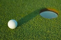 Sfera di golf sopra vicino al foro 1 Immagini Stock
