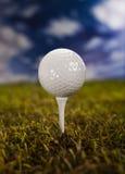 Sfera di golf su erba verde sopra un cielo blu Fotografia Stock