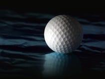 Sfera di golf su superficie riflettente fotografie stock libere da diritti