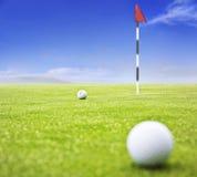 Sfera di golf su verde mettente Immagini Stock Libere da Diritti