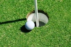 Sfera di golf sul foro vicino verde Immagine Stock
