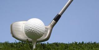 Sfera di golf sul T su erba con il driver Fotografia Stock