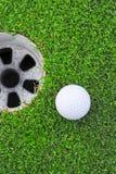 Sfera di golf sull'orlo della tazza fotografie stock
