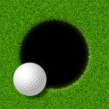 Sfera di golf sull'orlo della tazza Fotografia Stock